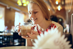 Girl is drinking latte in cafe. Stock Photos
