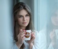 Portrait of a girl holding cup of coffee. Beautiful girl drinking coffee by the window in the morning Stock Photo