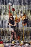 Portrait girl enjoying party and confetti. Happy young woman in fashionable clothes celebrating on a shimmer, colorful, party background. Party decorations gold stock images