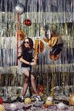Portrait girl enjoying party and confetti. Happy young woman in fashionable clothes celebrating on a shimmer, colorful, party background. Party decorations gold stock image