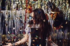 Portrait girl enjoying party and confetti. Happy young woman in fashionable clothes celebrating on a shimmer, colorful, party background. Party decorations gold stock photo