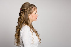 Portrait of a girl with a fashionable hairstyle in profile. Portrait of a girl with a fashionable hairstyle with curls in profile royalty free stock photos