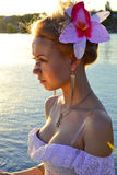 Portrait of a girl with a flower in nature. Portrait of a girl with a pink flower in her hair on the beach Stock Photos