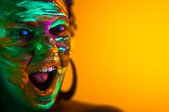 Portrait of girl with fluorescent paint makeup. Dye glowing near UV light. Woman with open mouth in neon light. Night royalty free stock image