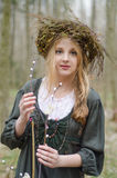 Portrait of a girl in a folk medieval style with willow branch. Portrait of a girl in a folk  medieval style with a circlet of flowers touching willow branch Stock Image