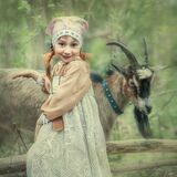 Portrait of a girl in the forest with a goat
