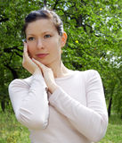 Portrait of girl in forest, hands near face Royalty Free Stock Images