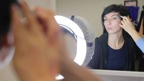 Portrait girl in front of the mirror with a brush makes make-up stock video