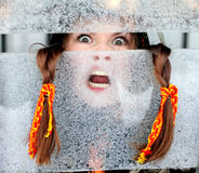 Portrait of a girl for a frosty window. Winter fun and ice. Canon 5Dmark2 Royalty Free Stock Photo