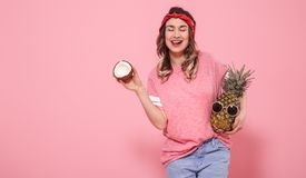 Portrait of a girl with fruit on a pink background stock photo