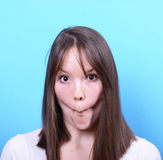 Portrait of girl with funny face against blue background Stock Photos