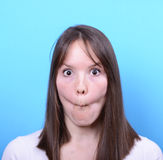 Portrait of girl with funny face against blue background Stock Photography