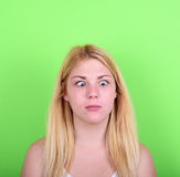 Portrait of girl with funny face against green background Stock Images