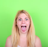 Portrait of girl with funny face against green background. This image is made in studio with model standing against colored backgrounds.Set of various conceptual Stock Photo
