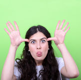 Portrait of girl with funny face against green background. This image is made in studio with model standing against colored backgrounds.Set of various conceptual Stock Images