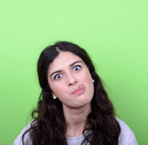 Portrait of girl with funny face against green background Stock Image