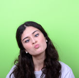 Portrait of girl with funny face against green background Stock Photo