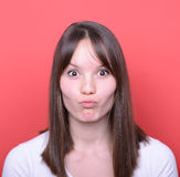 Portrait of girl with funny face against red background Stock Image