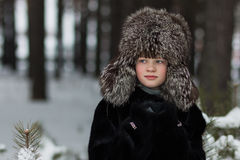 Portrait of a girl in a fur hat and fur coat frosty winter day in the forest Royalty Free Stock Images