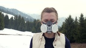 Portrait of a girl in gas mask looks at camera in nature. Woman in respirator stock video