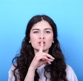 Portrait of girl with gesture for silence against blue backgroun Stock Photos