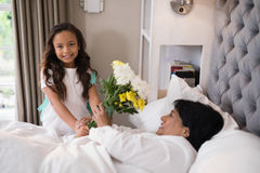 Portrait of girl giving bouquet to sick grandmother at home Royalty Free Stock Photography