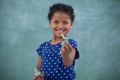 Portrait of girl giving paper currency Stock Photos