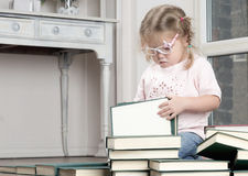 Portrait of a girl in glasses with books. The child sits at the window and studies the book Royalty Free Stock Image