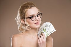 Portrait of a girl in glasses with money in hand. Close up portrait of a girl in glasses with money in hand on a beige background Stock Photos