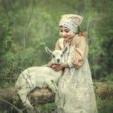 A little girl hugs a kid of goat