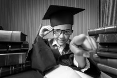 Portrait of girl in graduation cap and gown pointing at camera Stock Images