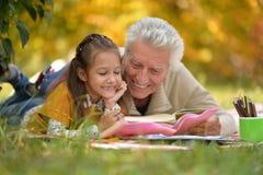 Girl and grandfather doing homework Royalty Free Stock Photos