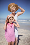 Portrait of girl with grandmother wearing sun hat at beach. During sunny day Stock Images