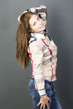 Portrait of a girl on a gray background. The girl dressed in jeans and a shirt Stock Photo