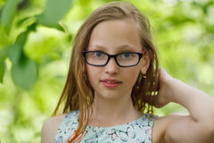 Portrait of girl in green forest. Twelve years old girl in glasses at green forest stock photography