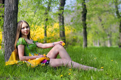 Portrait of girl in green grass. Beauty young girl sits on grass Royalty Free Stock Photos