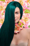 Portrait of a girl with green hair on floral background Stock Photo