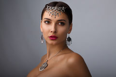 Portrait of a girl on a grey background with no clothes. women`s jewelry. Portrait of a beautiful girl with ornaments. pleasant appearance Stock Images