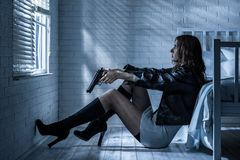 Portrait of a girl with a gun. Woman with gun in hand is sitting by the bed in the darkness Royalty Free Stock Image