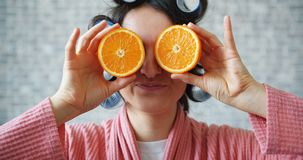 Portrait of girl with hair rollers holding oranges hiding eyes showing tongue. Portrait of joyful girl with hair rollers holding fresh oranges hiding eyes stock video