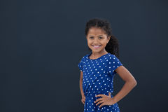 Portrait of girl with hand on hip. Standing against black background Stock Photo