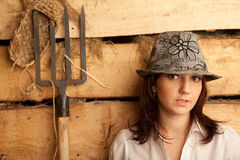Portrait of girl in hat in hayloft with pitchfork Stock Photography