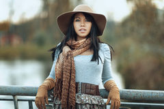 Portrait of  girl in a hat and scarf on the bridge. Portrait of a smiling beautiful brunette girl in a hat and scarf, she is standing on the bridge and looks Stock Images