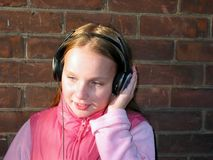 Portrait of a girl with headphones. Portrait of a young girl listening to music with headphones, brick wall background Royalty Free Stock Images