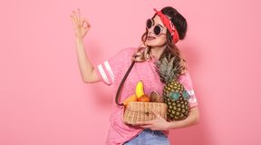 Portrait of a girl with healthy food, fruits, on a pink background royalty free stock images