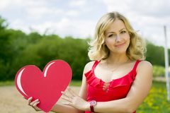 Portrait of a girl with a heart in his hands. The girl in the red dress.Love Royalty Free Stock Photos