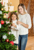 Portrait of girl helping beautiful young mother decorating Chris Stock Image