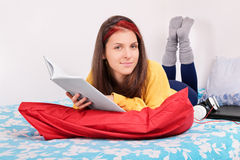 Portrait of a girl in her bed reading a book Stock Images