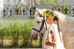 Portrait of a girl and her horse. Portrait of a girl in traditional Slavic dress with a wreath on his head with a beautiful white horse Stock Photo