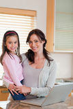 Portrait of a girl and her mother using a notebook Royalty Free Stock Photography